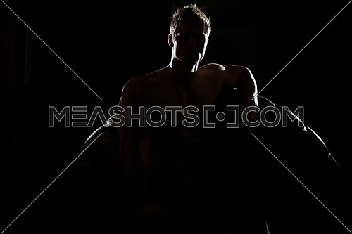 Siluet Portrait Of Muscular Young Man With Tire