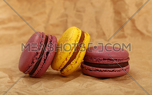 Group of several fresh colorful traditional French macaroon pastry cookies (macarons, macaroni) on brown paper parchment background, close up, low angle view