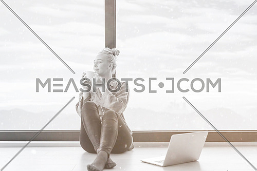Real Woman Using laptop on the floor Drinking Coffee Enjoying Relaxing at cold winter day