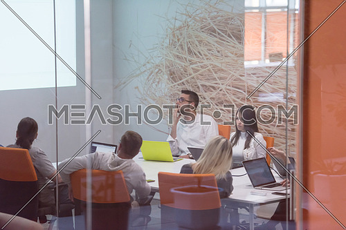 startup business, young creative people group brainstorming on meeting at office interior and using laptop computer to note ideas plans and projects