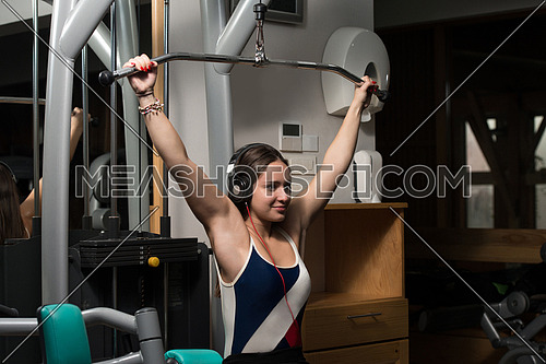 Young Woman Doing Heavy Weight Exercise For Back In Gym