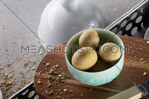Green olives in a green bowl on a wooden tray