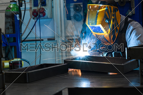Professional welder performs work with metal parts in factory, sparks, and electricity. Industry worker banner. High quality photo