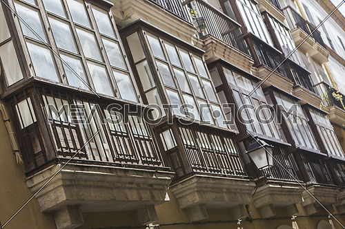 Cadiz Spain- March 31: Detail of balconies and large windows on the time of the nineteenth century, Narrow street with traditional architecture in Cadiz, Andalusia, southern Spain