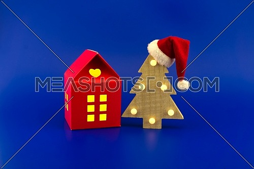 House shaped gift box with yellow glowing windows and stylized wooden Christmas tree with red Santa hat on a festive blue background. New Year and Christmas gift season concept