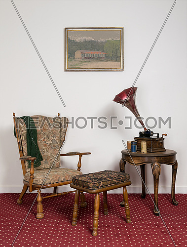 Retro ornate armchair, a 1911 old phonograph with three cylinder records on round coffee table and hanged painting on red carpet