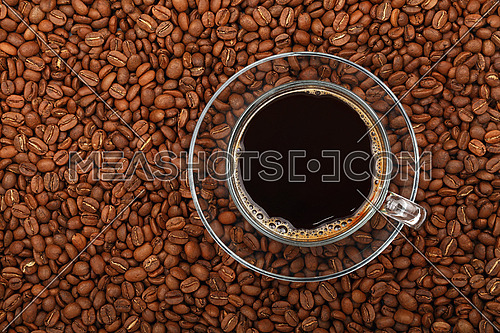 Full Americano black filtered coffee in transparent glass cup with saucer on background of roasted coffee beans, elevated top view, close up