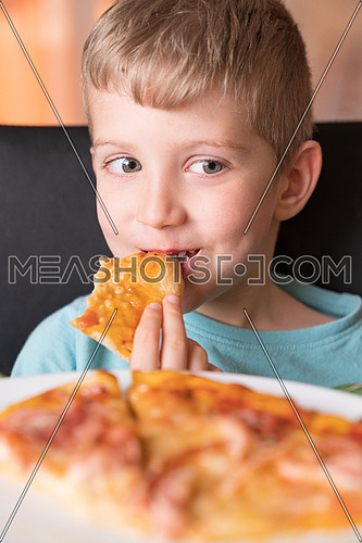 Beautiful happy young boy smiling and biting off slice of fresh made pizza,She sit at black chair, He has blonde hair.