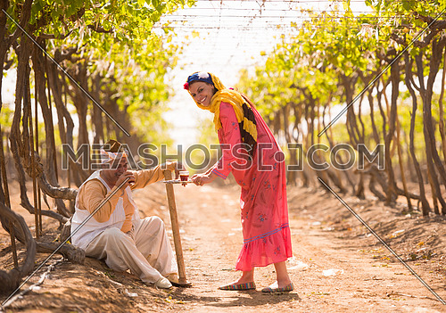 older middle eastern farmer and a young girl enjoyed sitting on the farm grapes