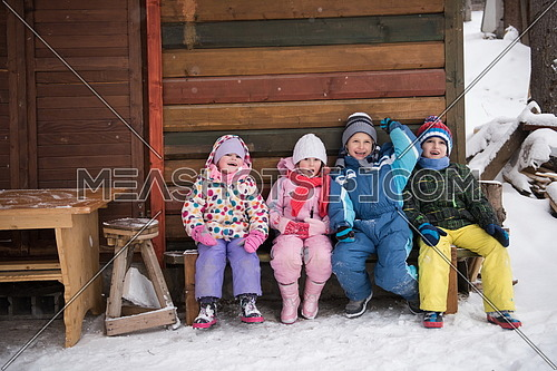 group portrait of kids, little child  group sitting together  in front of wooden cabin on vacation at beautiful winter  day with fresh snow