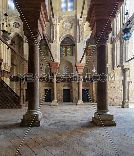 Interior of Sultan Qalawun Mosque with stone columns, colored stained glass windows and wooden doors, Cairo, Egypt