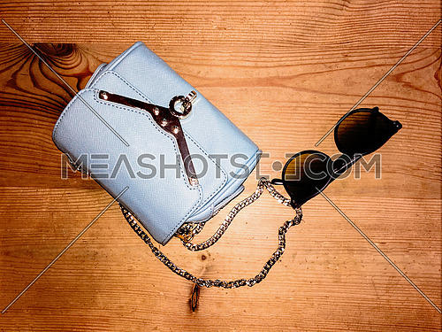 A light blue female bag and sunglasses on a wooden table top
