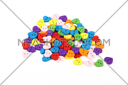 Mix of colorful multicolor heart shaped painted wooden handmade sewing buttons isolated on white, close up, high angle view