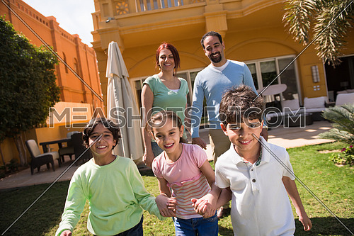 happy middle eastern young family enjoys a sunny day playing in the yard