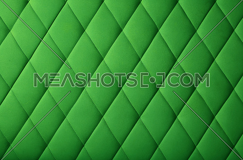 Background texture of green genuine leather soft tufted furniture or wall panel upholstery with deep diamond pattern, close up