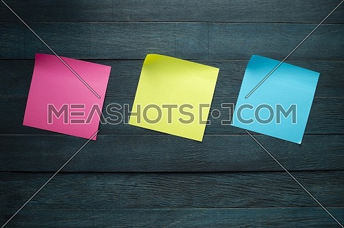 Pink yellow and blue blank adhesive note stickers with curled corners on blue rustic board. Free copy space for text