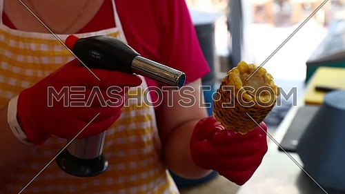 Closeup woman cooking steamed sweet corn cobs on stick with gas torch flame, low angle view