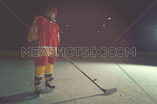 young teen girl ice hockey player portrait on training in black background