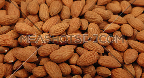 Whole raw brown almond nuts on retail market, close up, background, low angle view