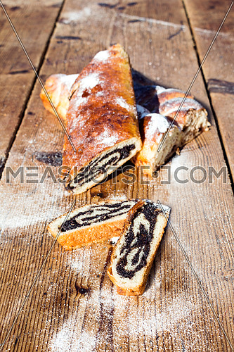 Strudel with poppy seeds on a Wooden Table All Sprinkeld With sugar Powder