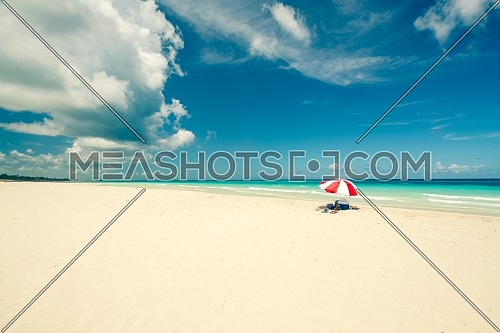 Beautiful beach of Varadero during a sunny day, fine white sand and turquoise and green Caribbean sea,on the right one red parasol,Cuba.concept photo,copy space,vintage style.