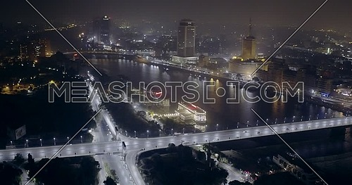 Aerial Shot flying around the River Nile showing Bridge, Hilton Hotel and Television Network Building in cairo at night