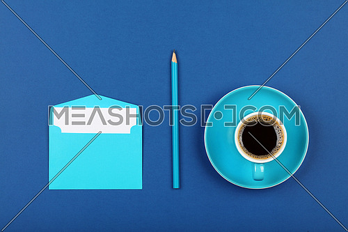 One open blank pastel blue envelope with white paper, black coffee cup and wooden pencil over dark indigo blue background, flat lay, directly above