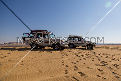 Two 4x4 cars parked in the desert