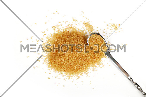 Metal spoon full of brown cane sugar with pinch of sugar spilled around isolated on white background, close up, elevated top view