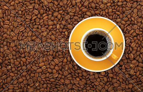 Full Americano black filtered coffee in small yellow cup with saucer on background of roasted coffee beans, elevated top view, close up