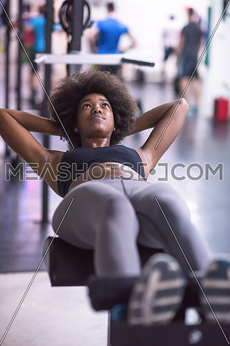 young fit african american woman doing sit ups in fitness studio at the gym.Abdominal exercises Sit up