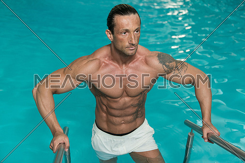 Happy Attractive Muscular Mature Man Resting Relaxed On Edge Of Swimming Pool