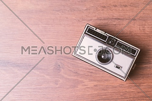 Retro classic 35mm photo camera on wooden Background