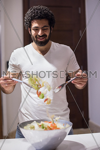 young middle east  man preparing salad in the kitchen with satisfaction