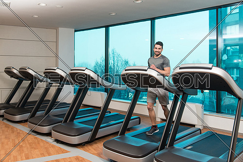 Handsome Man Running On The Treadmill In Gym