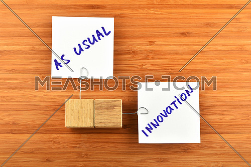 Innovation, two white paper notes with wooden holders in different directions on wooden bamboo background for presentation