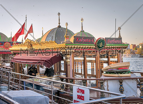 Istanbul, Turkey - April 25, 2017: Chefs preparing food in a traditional fast food bobbing boat serving fish sandwiches at Eminonu