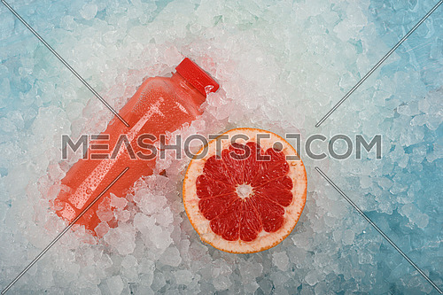 Close up one plastic PET bottle of fresh pink grapefruit juice and cut half orange slice over background of crushed ice, elevated high angle view, directly above