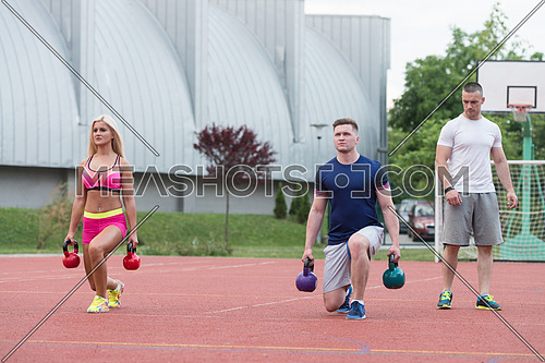 Group Of Young People Doing A Kettle Bell Exercise Outdoor With Instructor