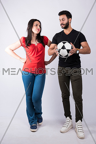 young couple standing and cheering on white background, while both of them having fun with a ball