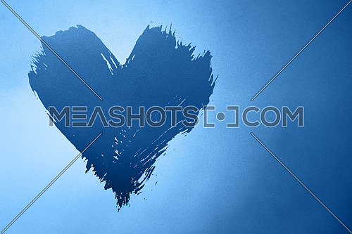 Abstract colorful background with brushstroke painted grunge blue heart over gradient noise grain texture with copy space