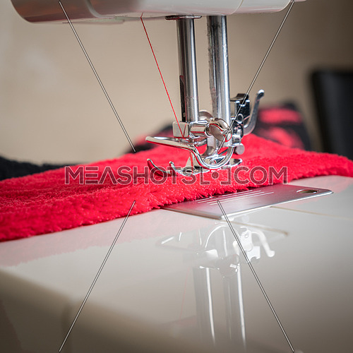 sewing machine close up and red cloth, sewing process in the phase of overstitching