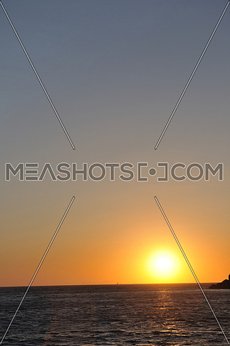 romantic sunset at sea eith tourist and travel boats on horizon