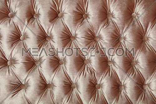 Light beige velvet capitone textile background, retro Chesterfield style checkered soft tufted fabric furniture diamond pattern decoration with buttons, close up