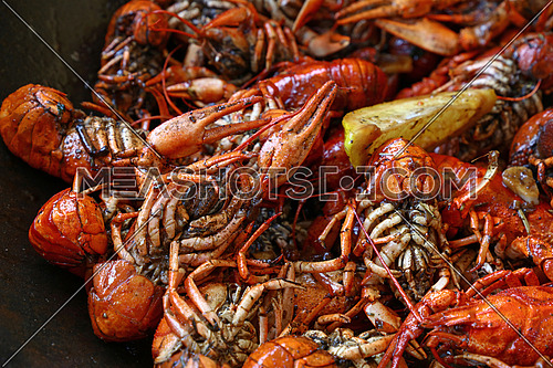 Portion of cooked ready to eat red crawfish (crayfish) with lemon in frying pan close up, high angle view
