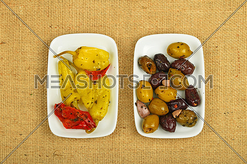 Mediterranean snack of red and green olives and pickled green pepper in two white plates on burlap jute canvas