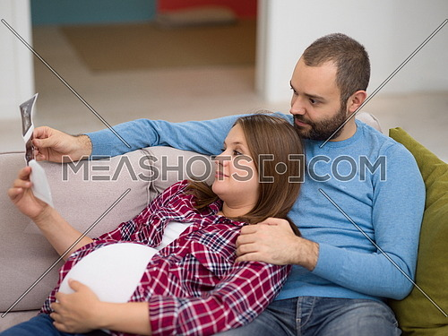 Young pregnant couple looking baby's ultrasound photo while relaxing on sofa at home