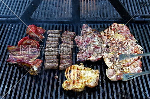Meat grilling over the hot coals on barbeque