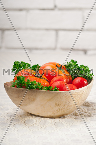 fresh ripe organic  tomatoes on a wood bowl with parsley