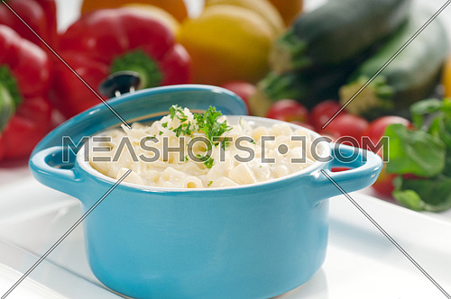 macaroni and cheese,kids favourite dish , on a blue little childish clay pot with vegetables on background,MORE DELICIOUS FOOD ON PORTFOLIO